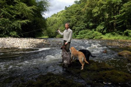 Photo of Dougy fishing on the Ericht with his dogs